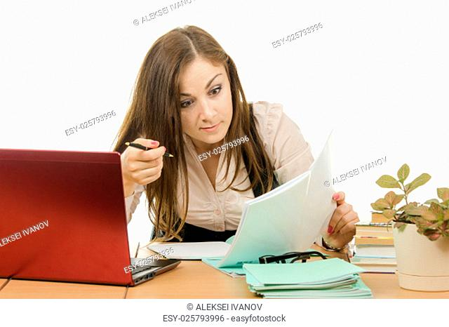 Cute little girl is a teacher sitting at a desk with a laptop, books and notebooks