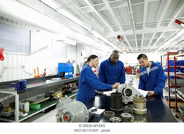 Helicopter mechanics examining parts in workshop