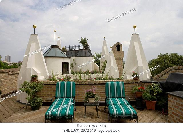 PATIOS: upper wood deck, two chaise lounges face camera, built in flower boxes into walls of roof, white geometric turrets