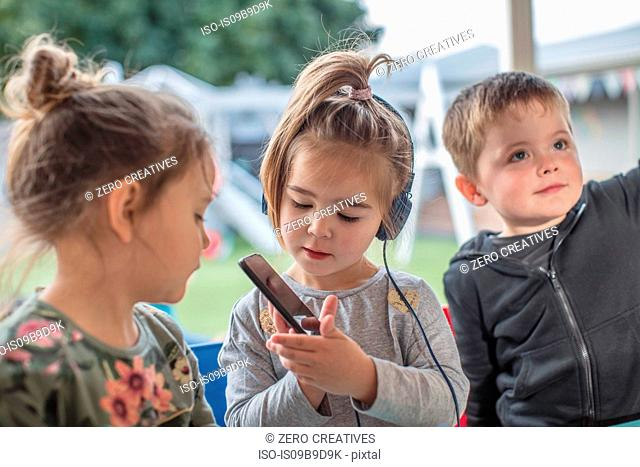 Young girl with friends, using smartphone, wearing headphones