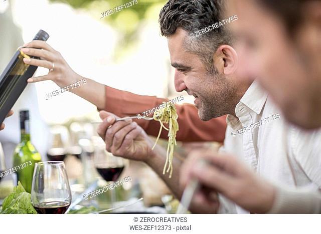 Man eating spaghetti for lunch in garden