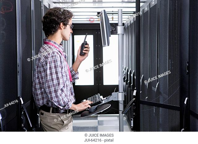 Technician, on walkie talkie, working on computer in aisle of server storage cabinets