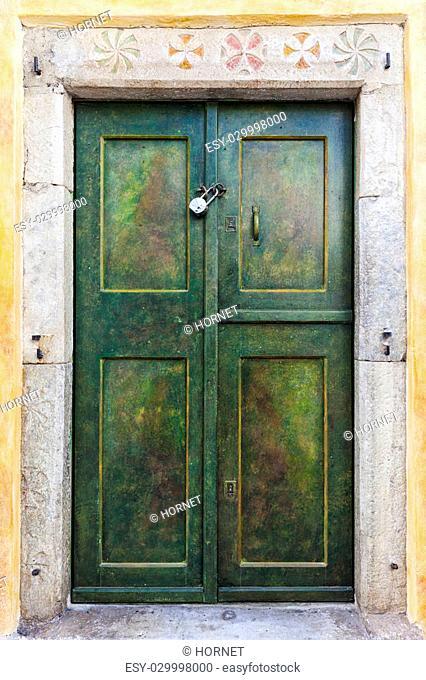 Green door with yellow wall in Santorini
