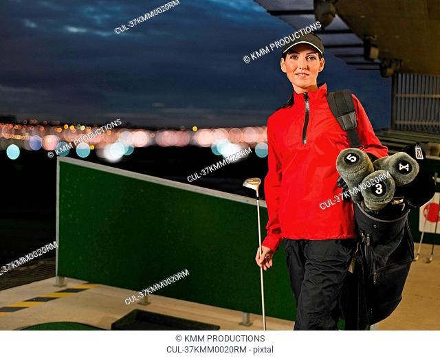 Woman with golf clubs at driving range