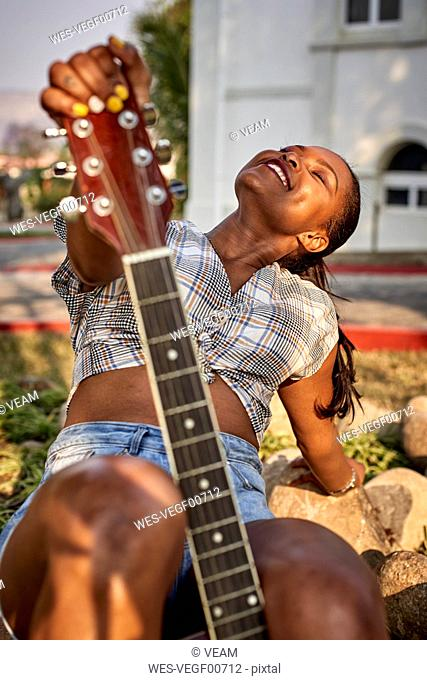 Smiling woman with guitar sitting outdoors