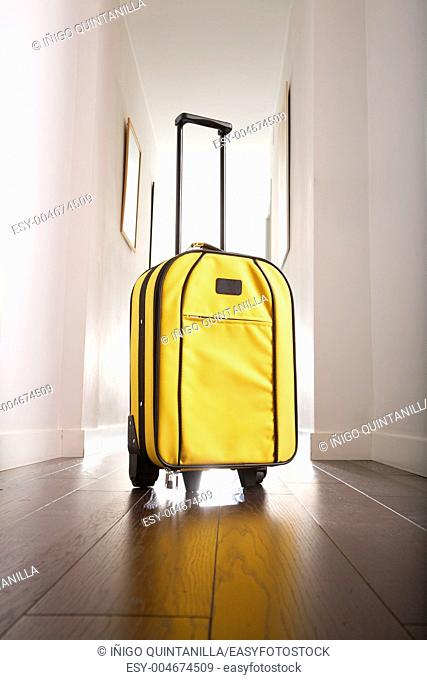 yellow suitcase standing at hall house with white corridor