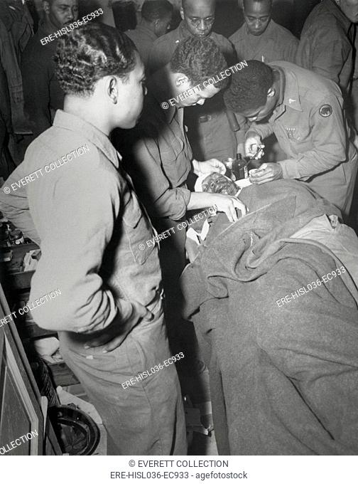 African American Army surgeon stitches face and shoulder wounds in the Pietrasanta Area, Italy. Feb. 10, 1945. Capt. Ezekia Smith, 370th Inf. Regt