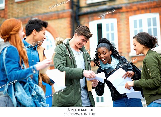 Happy young adult college students reading exam results on campus