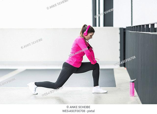 Woman wearing headphones stretching