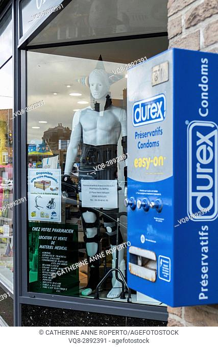 Rubber clad plastic mannequin next to Durex condom machine in town square pharmacy, Berques, France