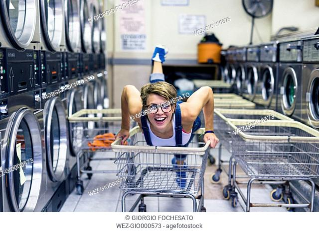 Portrait of smiling blond woman in a laundry