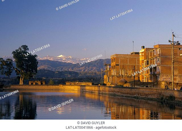 Hunamante River. River. Wall. Buildings. Tree. View to mountains. Wooded. Snowcapped