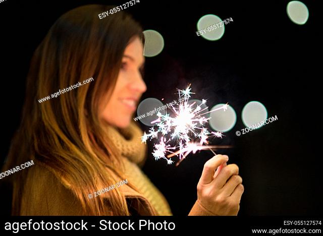 woman having fun with sparkler in her hands