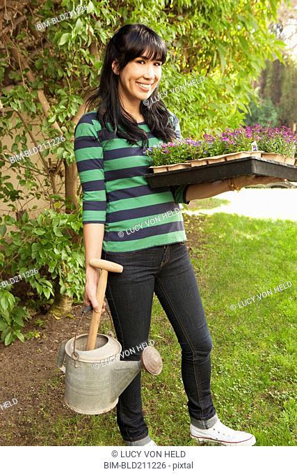 Woman carrying flower starts in backyard