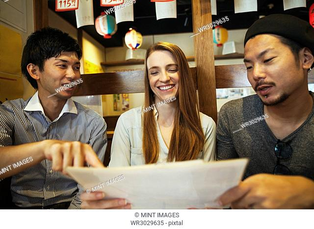 Three smiling people, woman and two men, sitting side by side at a table in a restaurant, looking at menu