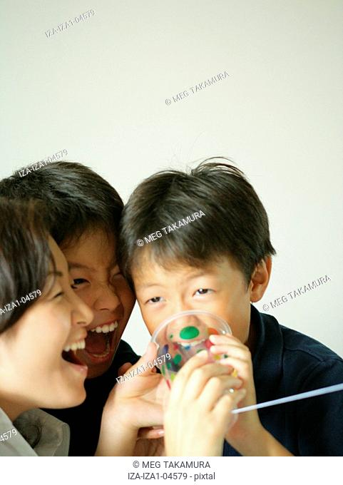Close-up of a mid adult woman and her two children playing with a tin can phone