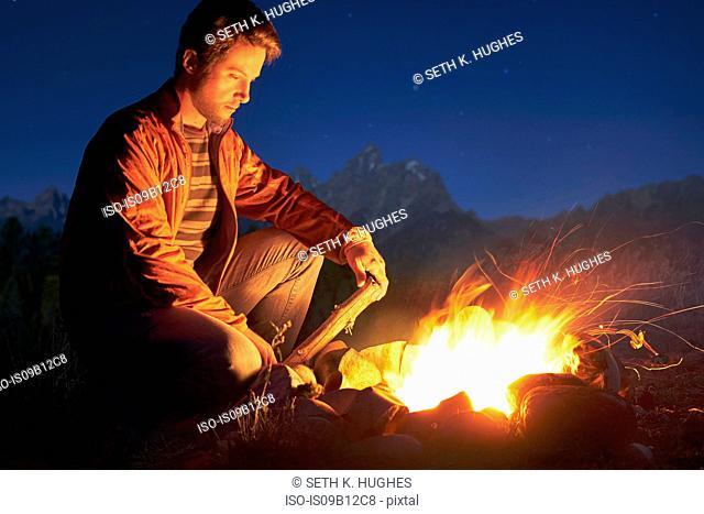 Man crouching by campfire at night, Jackson, Wyoming, USA