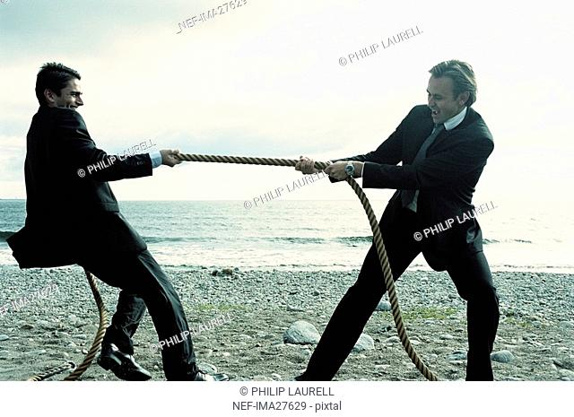 Two businessmen playing tug of war on riverbank
