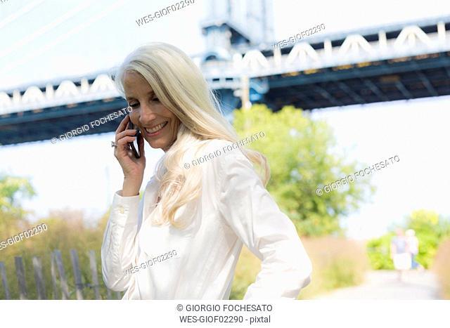 USA, Brooklyn, smiling mature woman on the phone in front of Manhattan Bridge