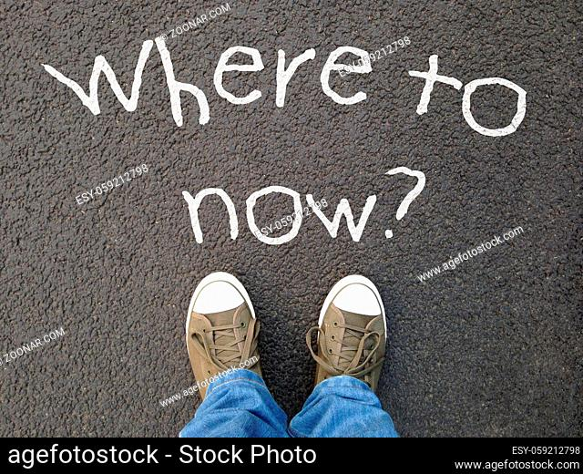 feet standing on road with where to now question written on asphalt - indecision confusion choice uncertainty concept