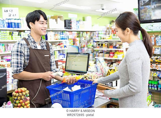 Smiling salesman and customer at supermarket