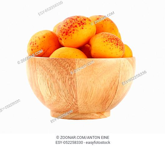 Mellow ripe fresh apricots with in small wooden bowl isolated on white background, close up, side view