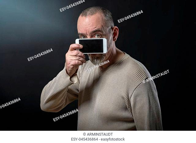 old man does not understand his smartphone