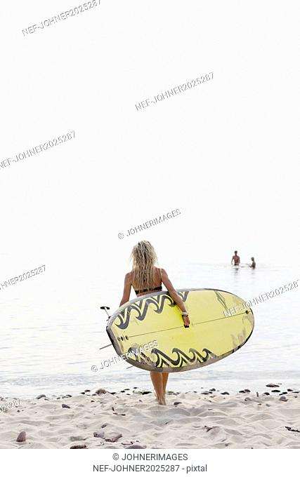 Young woman with paddleboard on beach