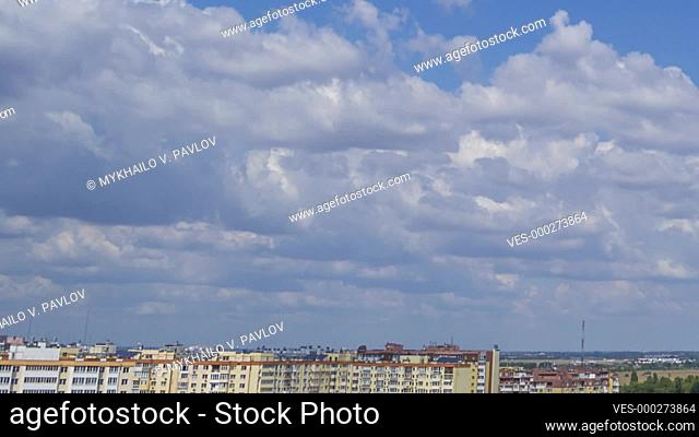 Sunny summer day over the rooftops of the city. The clouds are running fast in the blue sky. Panorama. Time lapse