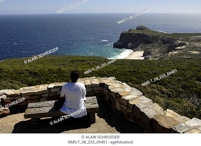 Rear view of a person sitting at the seaside, Cape Of Good Hope, Cape Peninsula National Park, Cape Town, Western Cape Province, South Africa