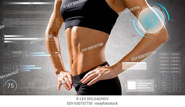 sport, fitness and people concept - close up of young woman in sportswear posing and showing muscles over gray background