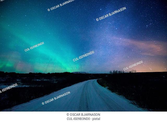 Road under aurora borealis at night, Thingvellir, Iceland