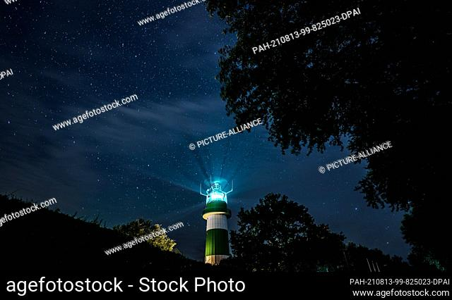 13 August 2021, Schleswig-Holstein, Strande: Countless stars stand in the sky above the Bülk lighthouse on the shore of the Baltic Sea