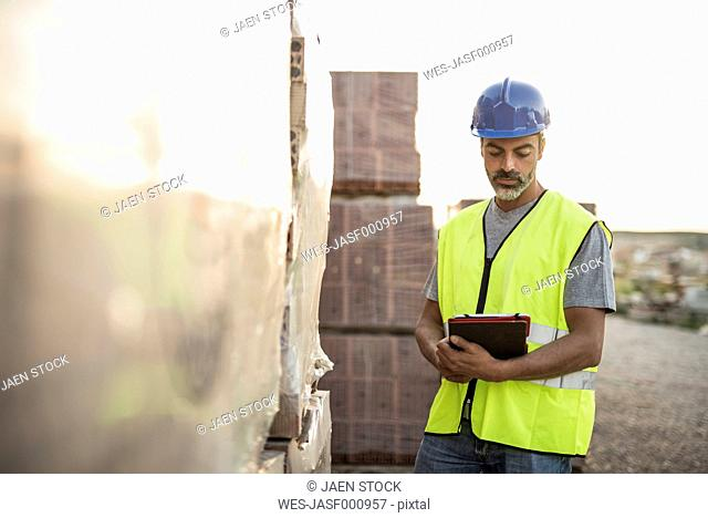 Construction worker checking building materials