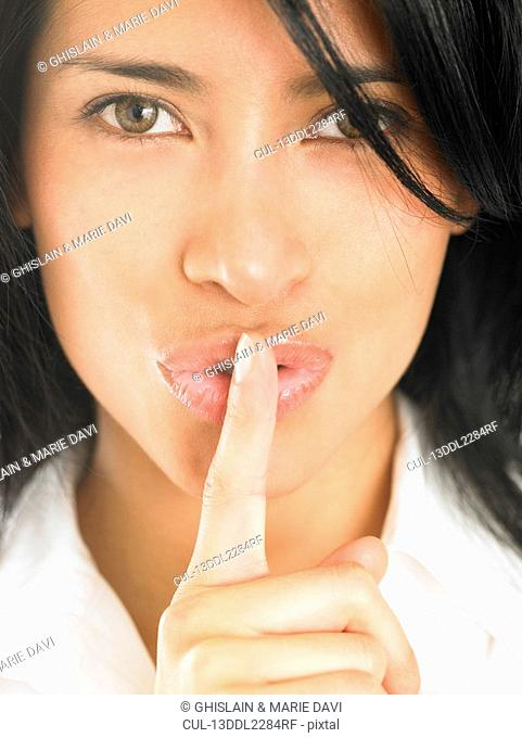 Woman with finger over her mouth