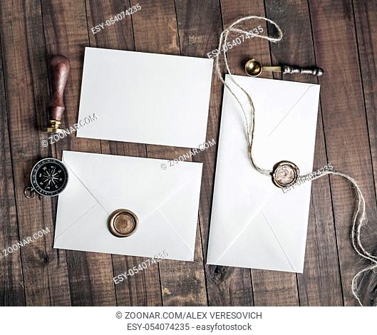 Vintage letter envelopes with wax seal, stamp, spoon, magnifier, compass and postcard on wood background. Flat lay