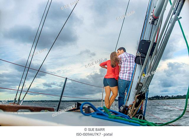 Rear view of couple on bow of boat kissing
