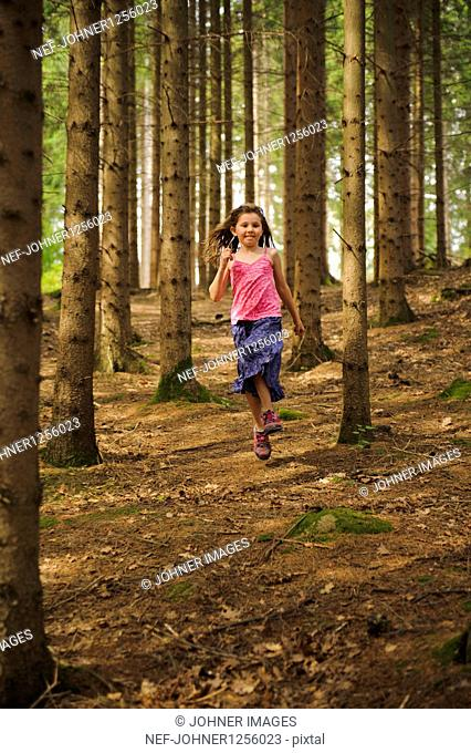 Girl running and playing in forest