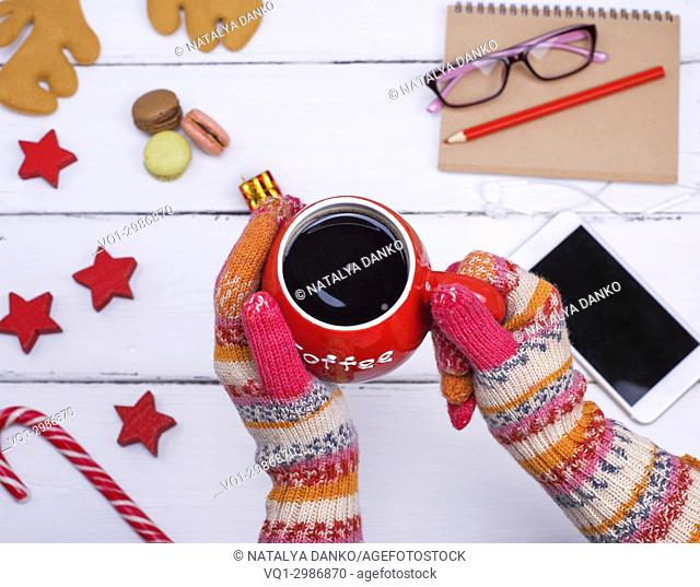 red cup of black coffee in female hands on which knitted winter gloves are dressed, top view