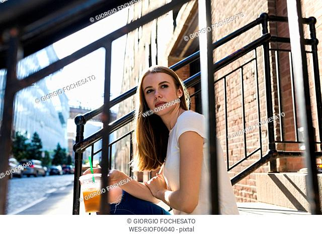 Young woman exploring New York City, sitting on stairs, drinking coffee