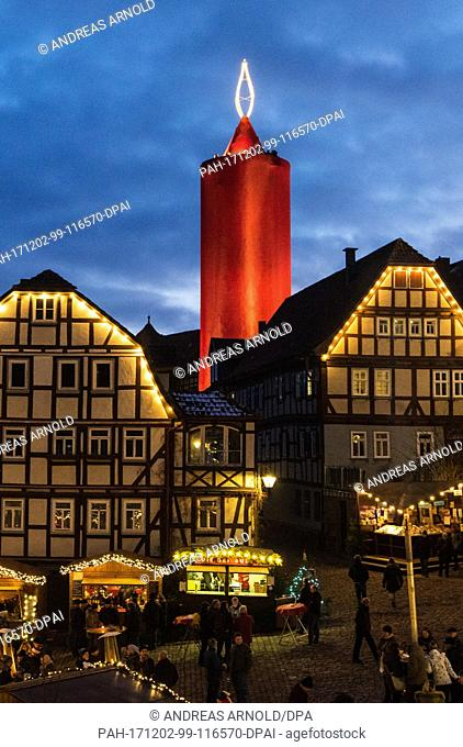 The world's largest candle shines at the Christmas market in Schlitz, Germany, 02 December 2017. A 36 metre high stone tower is wrapped in a red cloth every...