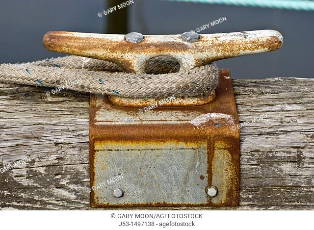 Cleat on harbor dock with line from docked boat