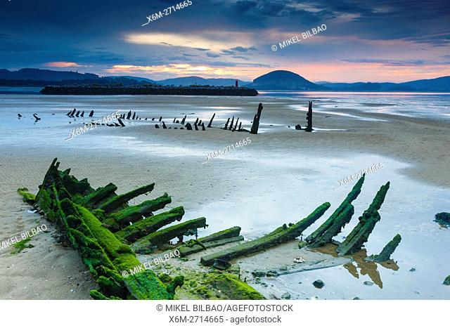 Tidal beach and boats remains at sunset. Santoña, Victoria and Joyel Marshes Natural Park. Colindres, Cantabria, Spain