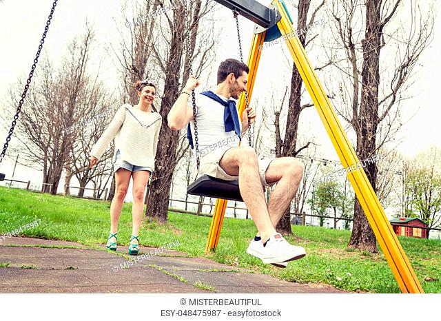 young woman pushes her boyfriend on the swing outdoor in the park