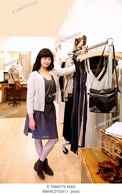 Mixed race business owner standing in clothing store
