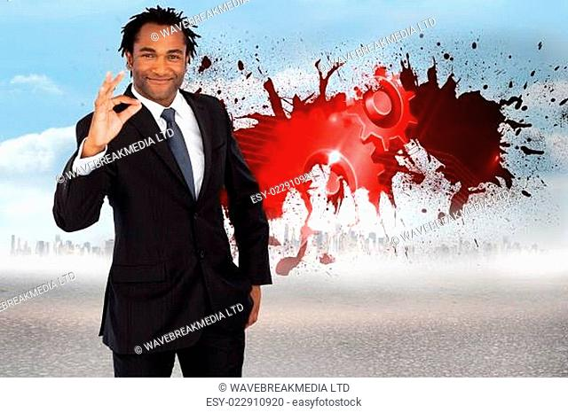 Composite image of businessman showing okay sign