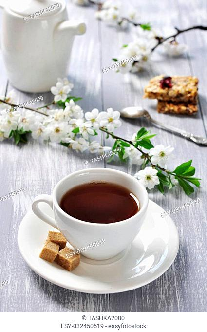 Cup of tea and teapot with branches of blooming cherry on wooden background