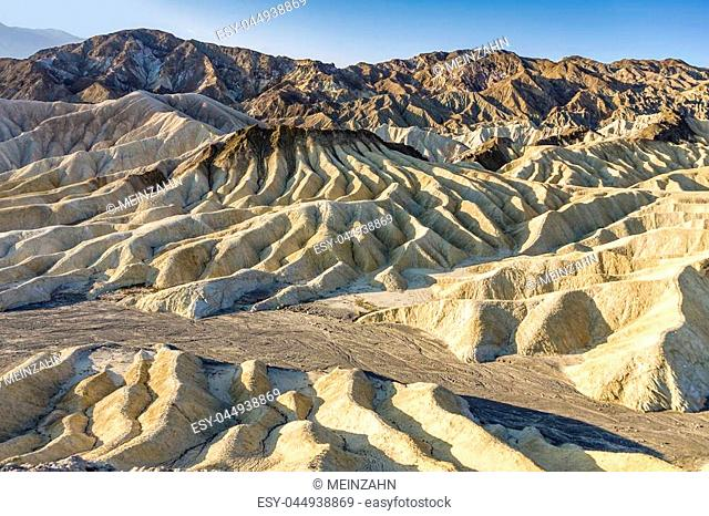Picturesque soft waves from multi-coloured sandstone. Death valley, Zabriski - a point on a sunset