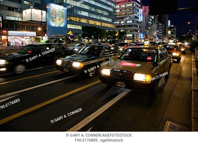 Blur of taxis at dusk in Omotesando, Tokyo, Japan