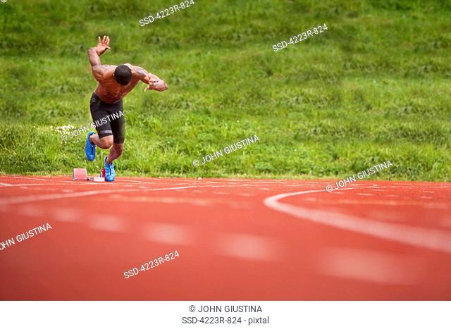 Male sprinter exploding out of blocks